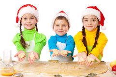 Three smiling kids showing Christmas cooking Stock Image