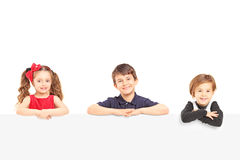 Three smiling kids standing behind a blank panel Royalty Free Stock Photo