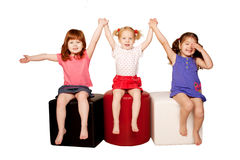 Three smiling little girls holding hands. Happy smiling children holding hands. Isolated on white background royalty free stock photography