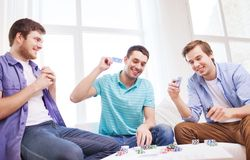 Three smiling male friends playing cards at home Stock Photos