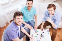 Three smiling male friends playing cards at home Royalty Free Stock Images