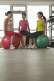 Three smiling mature women exercising with fitness balls in the gym Stock Images