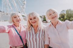 Three smiling older ladies are taking photo on camera stock photo