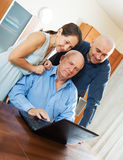 Three smiling people with laptop. Adult son halping his perents with laptop Stock Photography