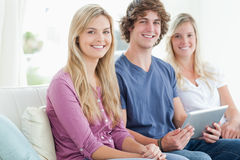 Three smiling people sit together on the couch with a tablet Stock Photos