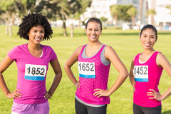 Three smiling runners supporting breast cancer marathon Royalty Free Stock Image