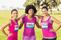 Three smiling runners supporting breast cancer marathon. Portrait of three smiling runners supporting breast cancer marathon in parkland Royalty Free Stock Photos
