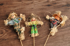 Three smiling scarecrows. Isolated against a wooden background Royalty Free Stock Photo