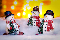 Three smiling snowmen in snow, Happy New Year 2017, Christmas Royalty Free Stock Photos