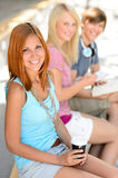 Three smiling student friends sitting summer Stock Image