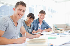 Three smiling students doing homework as they look into the came Stock Images