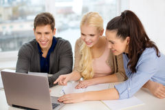Three smiling students with laptop and notebooks. Education, technology, school and internet concept - three smiling students with laptop and notebooks at school Royalty Free Stock Image