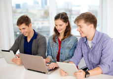 Three smiling students with laptop and tablet pc Stock Photo
