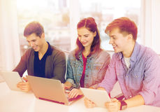 Three smiling students with laptop and tablet pc Royalty Free Stock Image