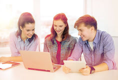 Three smiling students with laptop and tablet pc Stock Photography