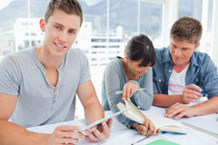 Three smiling students sitting and doing work Stock Image