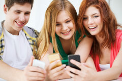 Three smiling students with smartphone at school Royalty Free Stock Photos