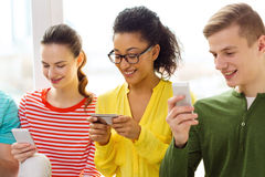 Three smiling students with smartphone at school. Education, relationships and technology concept - three smiling students with smartphone at school stock photo