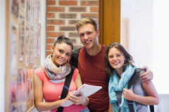 Three smiling students standing next to notice board Royalty Free Stock Photography