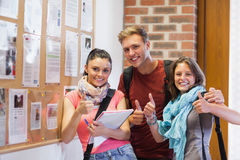 Three smiling students standing next to notice board showing thumbs up Stock Image