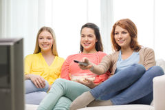 Three smiling teenage girl watching tv at home Stock Photo