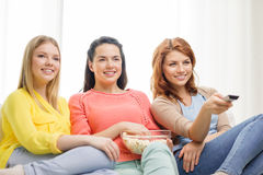 Three smiling teenage girl watching tv at home Stock Photos