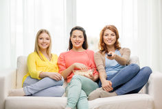 Three smiling teenage girl watching tv at home. Home, technology and friendship concept - three smiling teenage girl watching tv at home and eating popcorn Stock Photography