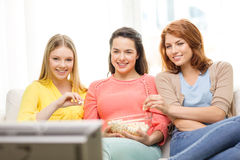 Three smiling teenage girl watching tv at home. Home, technology and friendship concept - three smiling teenage girl watching tv at home and eating popcorn stock images