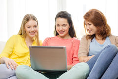 Three smiling teenage girls with laptop at home. Friendship, technology and internet concept - three smiling teenage girls with laptop computer at home Stock Photo