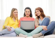 Three smiling teenage girls with laptop at home. Friendship, technology and internet concept - three smiling teenage girls with laptop computer at home Royalty Free Stock Images