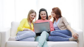 Three smiling teenage girls with laptop at home stock video footage