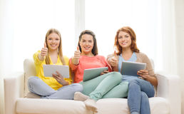 Three smiling teenage girls with tablet pc at home Royalty Free Stock Photography