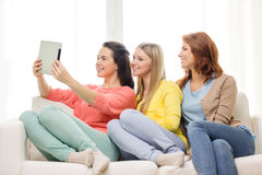 Three smiling teenage girls with tablet pc at home Stock Images