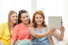 Three smiling teenage girls with tablet pc at home Stock Photography