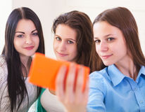 Three smiling teenage girls taking selfie with smartphone camera Stock Photos