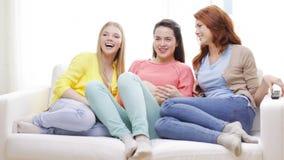 Three smiling teenage girls watching tv at home stock footage