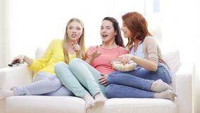 Three smiling teenage girls watching tv at home Royalty Free Stock Photos