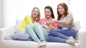 Three smiling teenage girls watching tv at home Royalty Free Stock Photography