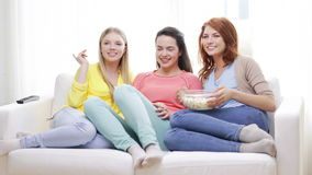 Three smiling teenage girls watching tv at home Stock Photo