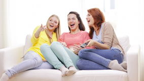 Three smiling teenage girls watching tv at home stock video footage