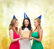 Three smiling women in blue hats with gift box Stock Photography
