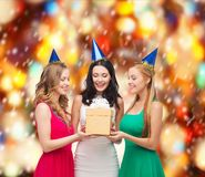 Three smiling women in blue hats with gift box Stock Images