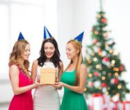Three smiling women in blue hats with gift box Stock Photos