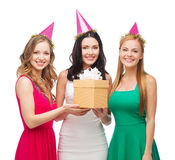Three smiling women in blue hats with gift box Royalty Free Stock Photo