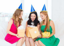 Three smiling women in blue hats with gift boxes Royalty Free Stock Photos