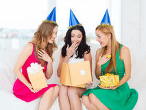 Three smiling women in blue hats with gift boxes Stock Photography
