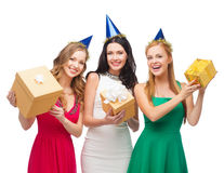Three smiling women in blue hats with gift boxes Stock Photos