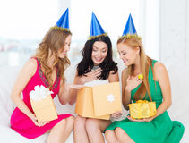 Three smiling women in blue hats with gift boxes Royalty Free Stock Images