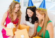 Three smiling women in blue hats with gift boxes Royalty Free Stock Photo