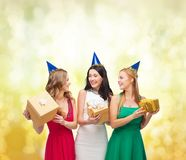 Three smiling women in blue hats with gift boxes Royalty Free Stock Photography